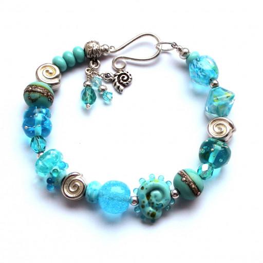 Armband mit Hakenverschluss, versiölberten Schnecken und vielen verschiedenen türkisen Perlen aus Muranoglas