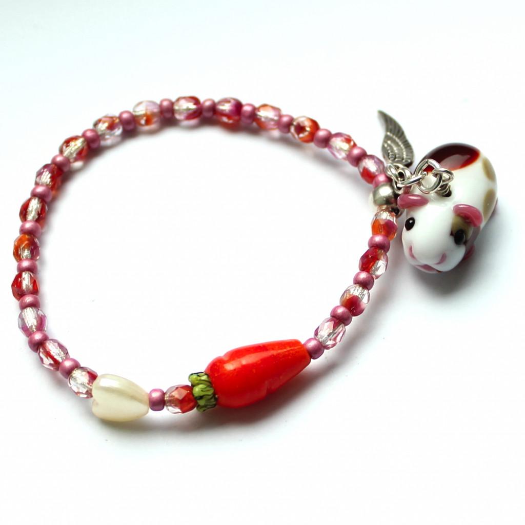 Armband aus orang-pinken Glasschliffperlen mit Karotte und Herzchen. Als Anhänger hängt ein kleines Meerschweinchen aus Muranoglas mit Silberflügel dran.