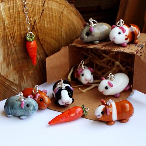 Meerschweinchen aus Muranoglas zu Kettenanhängern verarbeitet tummeln sich auf einer Schachtel die als Stall fungiert
