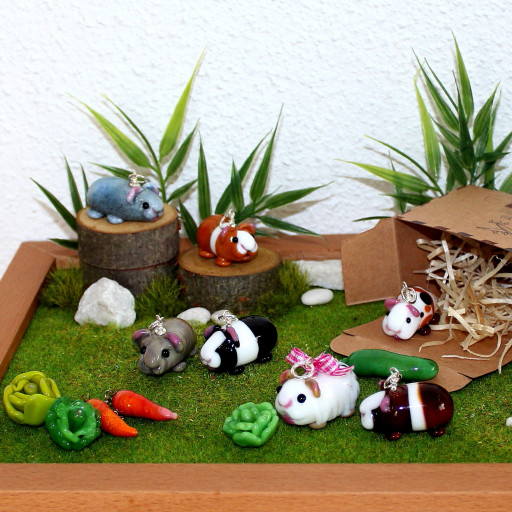 Meerschweinchen tummeln sich auf der Wiese, um sie herum liegt ihr Futter: Kopfsalat, Karotten, Gurke. Alles ist aus Muranoglas gefertigt.