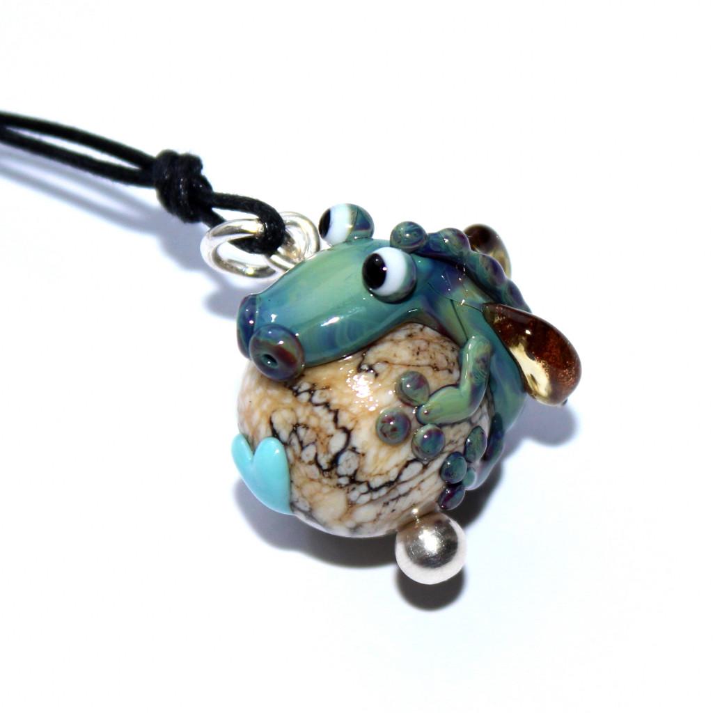 Türkiser Drache auf naturfarbener Kugel mit helltürkisem Herz zu einem Anhänger verarbeitet
