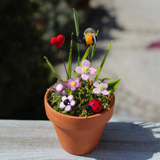 Hummel, Marienkäfer und Herz in rosa Blüten aus Glas im Tontopf mit Moos