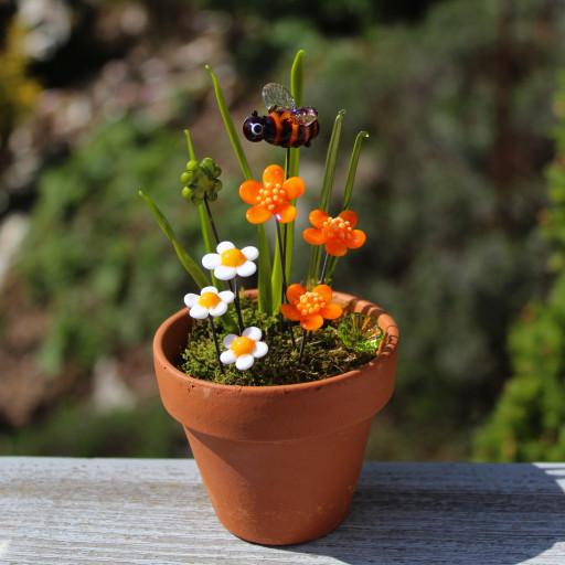 Biene mit orangen Blüten, Glücksklee und Gänseblümchen aus venezischem Glas, Muranoglas, im Tontopf mit Moos.