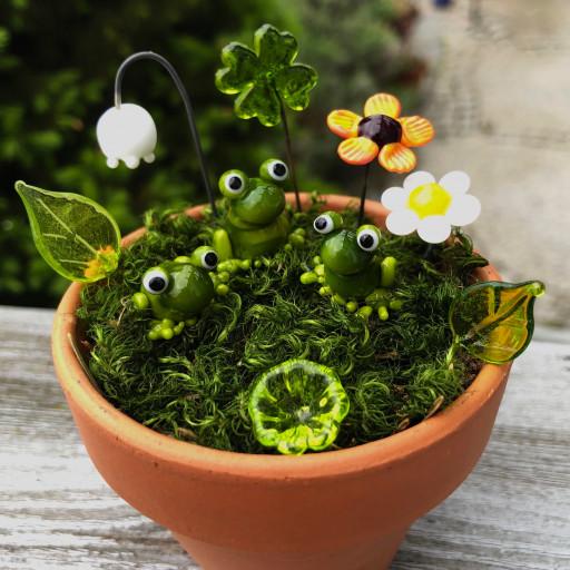 Drei Frösche sitzen auf der Wiese mit Blumen und Blättern - alles ist aus Muranoglas gefertigt und in einem Tontopf mit Moos arrangiert.